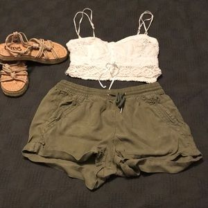 White crop top with arm green soft shorts.